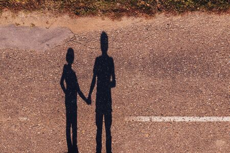 Shadow of couple holding hands, man and woman standing on asphalt road