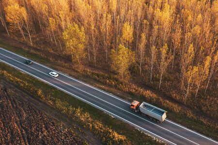Aerial view of traffic on road through autumnal cottonwood forest, truck and cars on roadway from drone pov