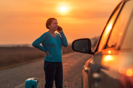 Woman calling roadside assistance after her car broke down in middle of nowhere, warm autumn sunset scenery, selective focus Zdjęcie Seryjne