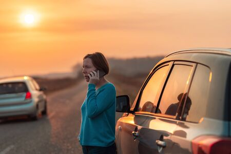 Woman calling on mobile phone for assistance and help on the road after her car broke down in autumn sunset on road through countryside, selective focus Zdjęcie Seryjne
