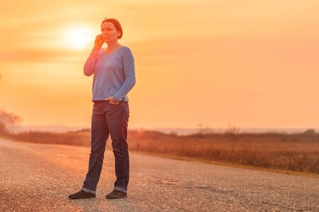 Woman standing on countryside road and talking on mobile phone in warm autumn sunset, selective focus
