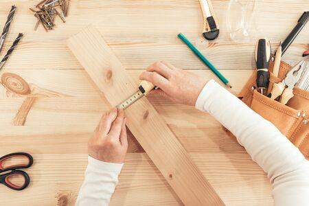 Top view of female carpenter hands working on desk in woodwork workshop Zdjęcie Seryjne