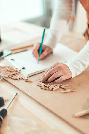 Female carpenter working with wooden dowels in carpentry woodwork workshop, selective focus Zdjęcie Seryjne