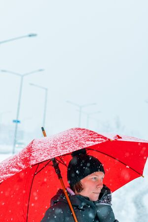 Pleasant woman talking on mobile phone under red umbrella while standing in the street in winter snow