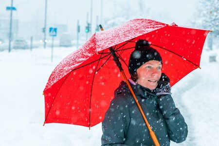Lively woman talking on mobile phone under red umbrella while standing in the street in winter snow Zdjęcie Seryjne