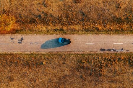 Car on the road through autumn countryside, aerial view directly above from drone pov Zdjęcie Seryjne