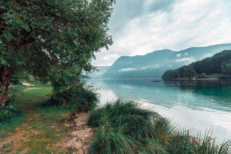 Overcast afternoon on Lake Bohinj, Slovenia. People enjoying outdoor water sport activities in bad weather