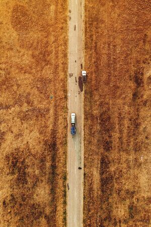 Aerial view of cars on plain countryside landscape road in autumn, drone pov