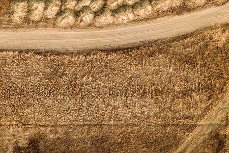 Aerial view of dusty dirt road through grassy plain landscape, top view from drone pov Zdjęcie Seryjne