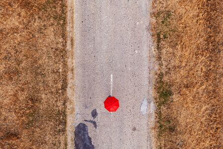 Red umbrella on road, top view from drone pov