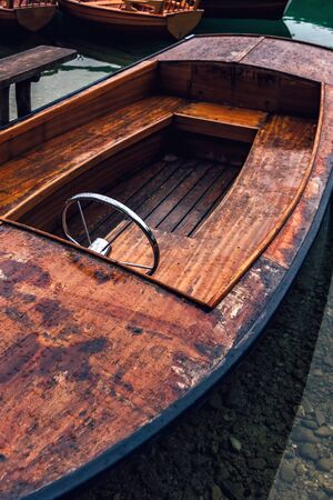 Wooden boat on lakeshore on rainy day