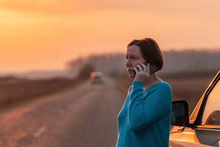 Woman talking on mobile phone by the stopped car on country road in autumn sunset Archivio Fotografico