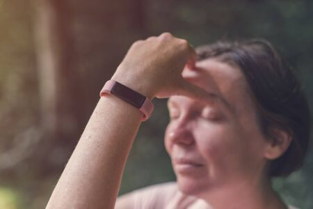 Female hiker with smart fitness tracker while resting in nature, selective focus Stock Photo