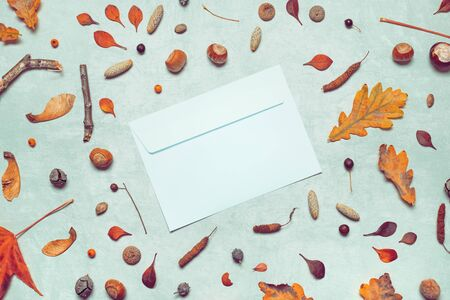 Blank post mail envelope mock up with autumn arrangement flat lay top view copy space
