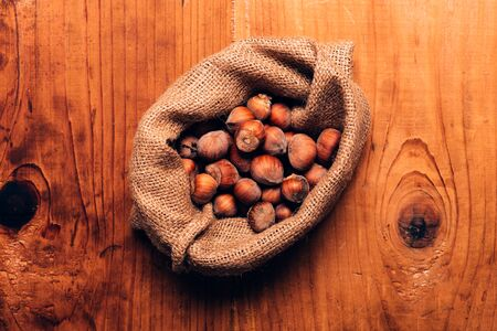 Hazelnut heap in burlap sack on wooden table, top view