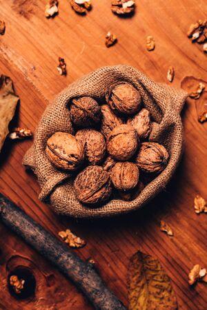 Walnut heap in burlap sack on wooden table, top view Banco de Imagens - 134791753