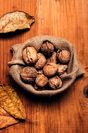 Walnut heap in burlap sack on wooden table, top view Banco de Imagens - 134791759