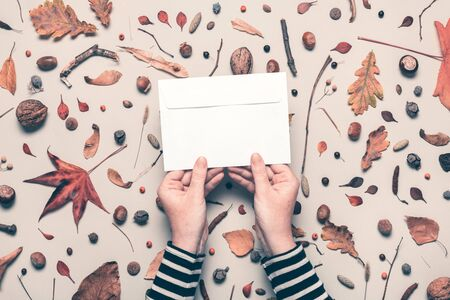 Woman holding blank post mail envelope mock up with autumn arrangement flat lay top view copy space
