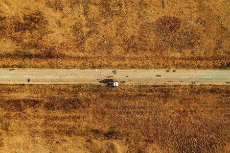 Abandoned car by the road, top view aerial photography from drone pov