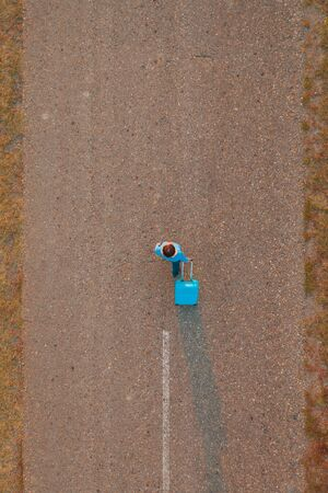 Woman pulling travel suitcase luggage on road in autumn sunset, high angle view from drone pov