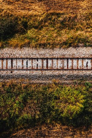 Old railroad track through countryside in autumn, aerial view from drone pov Фото со стока