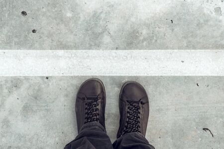 Standing at dividing line, male feet and shoes from above on concrete sidewalk with white line as border Фото со стока