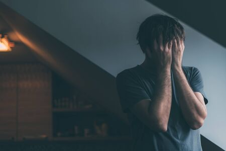 Depressed man is crying by the window of kitchen loft, hands covering face, selective focus