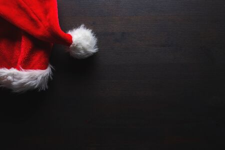 Santa Claus hat on dark wooden table as copy space, flat lay top view Фото со стока