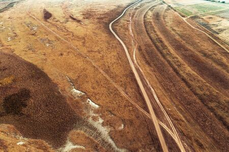 Aerial view of dusty dirt road in plain landscape from drone pov