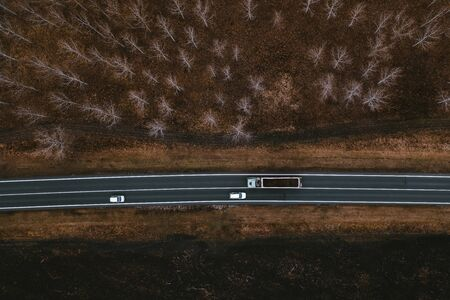 Two white cars and truck on the road, top-down shot aerial view from drone