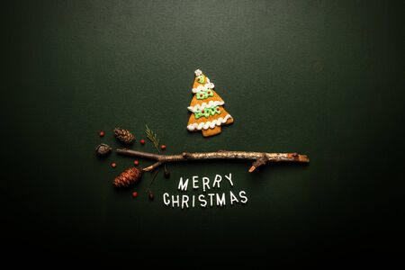 Merry Christmas text flat lay top view with gingerbread Christmas fir tree on green background, xmas holiday conceptual image