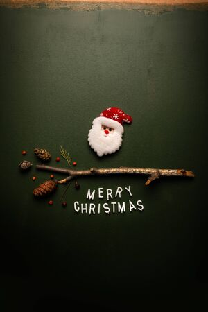 Merry Christmas text flat lay top view with Santa Claus on green background, xmas holiday conceptual image