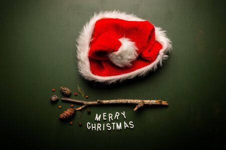 Merry Christmas text flat lay top view with Santa Claus hat on green background, xmas holiday conceptual image Banco de Imagens