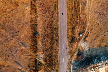 Top view of old worn road through grassy autumn meadow from drone pov Banco de Imagens