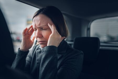 Businesswoman having migraine headache in company car while driving to work, selective focus Фото со стока
