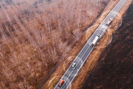 Aerial view of autonomous self-driving car on road through countryside from drone pov, conceptual image with digital enhancement
