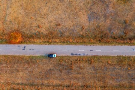 Woman and car on road through grassy wastelands, aerial view directly above from drone pov