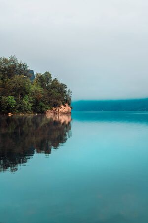Lake Bohinj in misty august morning, beautiful glacial lake situated in Slovenian Triglav national park