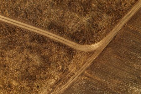 Aerial view of dusty dirt road through grassy plain landscape, top view from drone pov Banco de Imagens