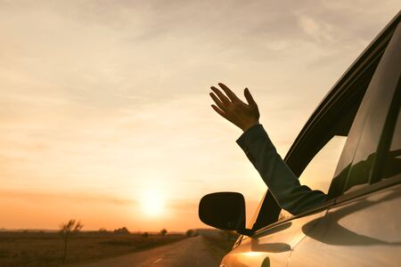 Feeling the wind while driving through countryside, woman reaching out hand from car window in autumn sunset, selective focus