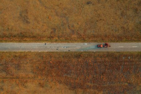 Old tractor on worn asphalt road through grassy countryside meadow, directly above from drone pov Banco de Imagens