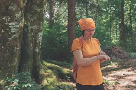 Woman hiker using smart wristband during trekking in nature. Female hiking in forest and checking on her modern gadget.