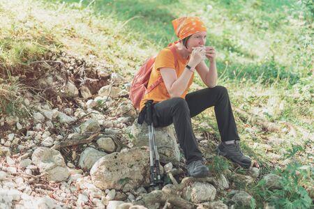 Female hiker eating sandwich in nature, taking a break from trekking outdoor activity and enjoying food 版權商用圖片