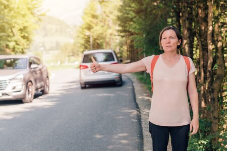 Female hiker hitchhiking on road through countryside on sunny summer day 版權商用圖片