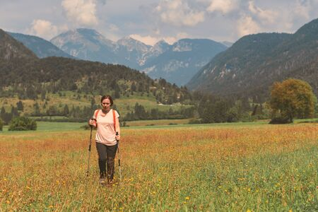 Female hiker is trekking in alpine countryside landscape in sunny autumn midday using hiking poles, selective focus