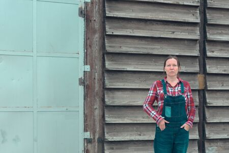 Portrait of female farmer in front of the farmhouse shed. Woman dressed in plid shirt and denim jeans overalls as farm worker with hands in pockets Stock Photo