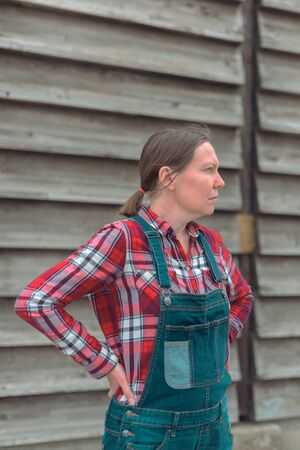 Portrait of female farmer in front of the farmhouse shed. Woman dressed in plid shirt and denim jeans overalls as farm worker with hands on hips