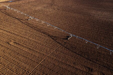 Aerial view of center-pivot irrigation system on plowed field from drone pov, agriculture and farming equipment