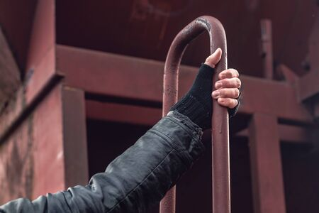 Homeless immigrant climbing on freight train, close up of hand, conceptual image with selective focus Reklamní fotografie