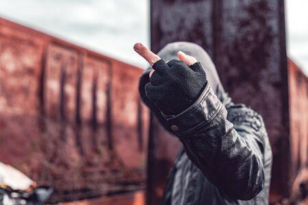 Drug addict gesturing middle finger, selective focus